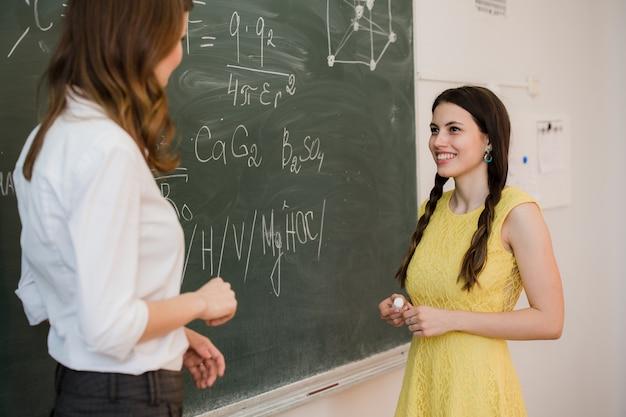 Menina responde a perguntas dos professores perto de um conselho escolar