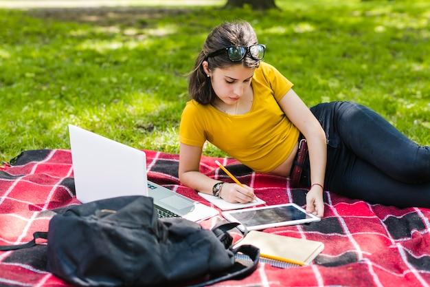 Menina responsável que estuda no parque Foto gratuita