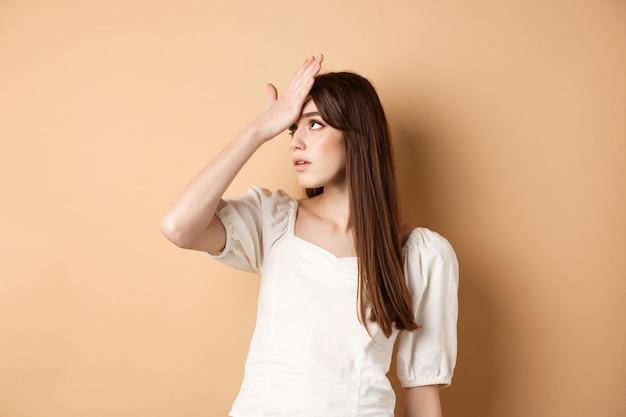 Menina revirando os olhos e dando um tapa na testa irritada, incomodada por algo estúpido ou coxo, fazendo cara palma no fundo bege.