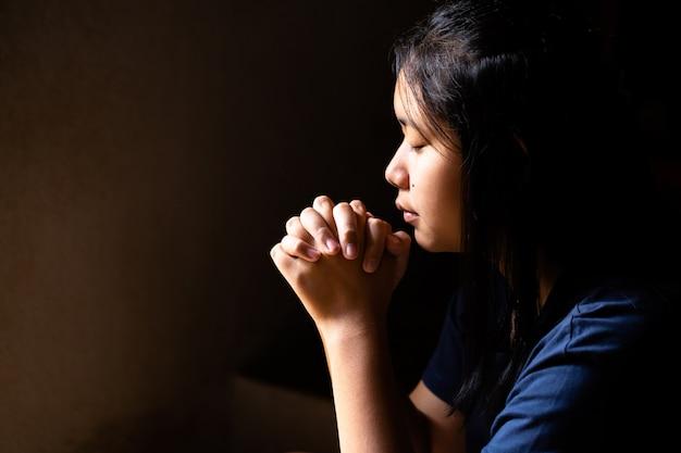 Menina rezando com os olhos fechados