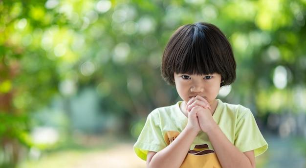 Menina rezando de manhã, mãos cruzadas em oração