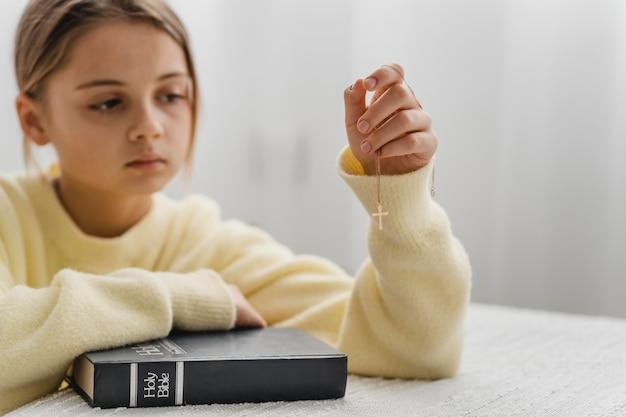 Menina rezando em casa com a bíblia e colar de cruz