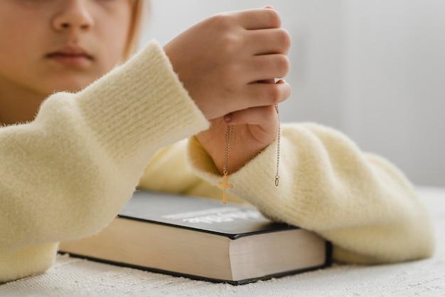 Menina rezando em casa com a bíblia e o colar da cruz