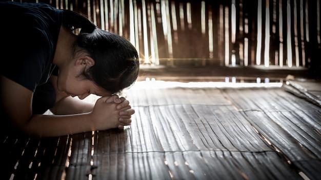 Menina rezando no log de madeira