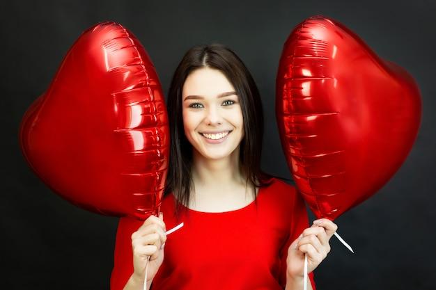 Menina ri lindamente segurando balões. uma bela morena sorridente está segurando dois balões em forma de coração perto do rosto.