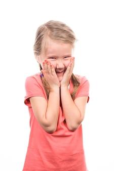Menina rindo com as mãos na boca