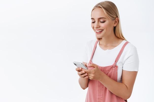 Menina rindo e olhando a tela do smartphone, recebe mensagem engraçada. mulher loira atraente, moderna, caucasiana, de macacão, camiseta, usa o celular, navega nas redes sociais e assiste a vídeos