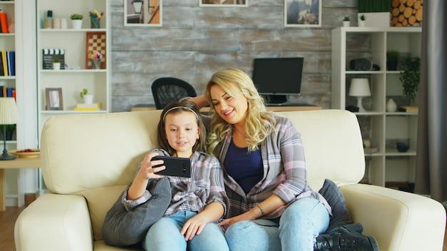 Menina rindo enquanto assiste a um vídeo no smartphone, sentada no sofá com a mãe.