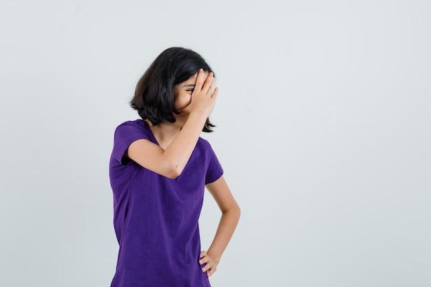 Menina rindo por trás da mão em uma camiseta e parecendo brincalhão.