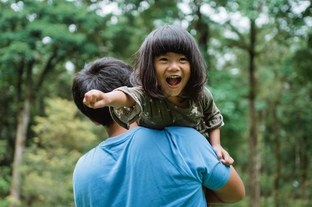 Menina riu alegremente quando carregada no ombro do pai