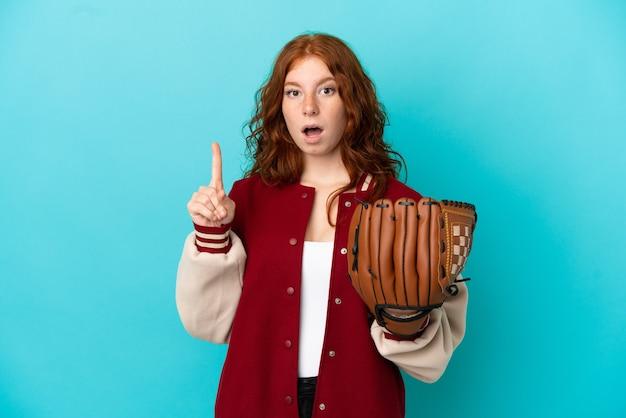 Menina ruiva adolescente com luva de beisebol isolada em um fundo azul com a intenção de perceber a solução enquanto levanta um dedo