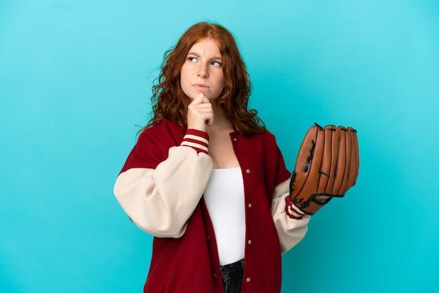 Menina ruiva adolescente com luva de beisebol isolada em um fundo azul, tendo dúvidas e pensando