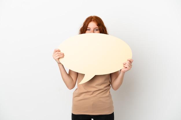 Menina ruiva adolescente isolada no fundo branco segurando um balão de fala vazio escondido atrás dele.