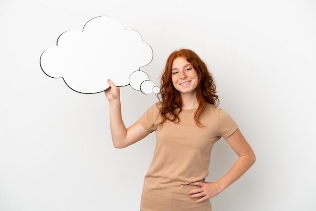 Menina ruiva adolescente isolada no fundo branco segurando um balão de pensamento