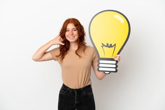 Menina ruiva adolescente isolada no fundo branco segurando um ícone de lâmpada e fazendo um gesto de telefone