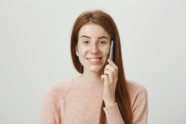 Menina ruiva alegre com sardas, sorrindo e falando ao telefone despreocupada