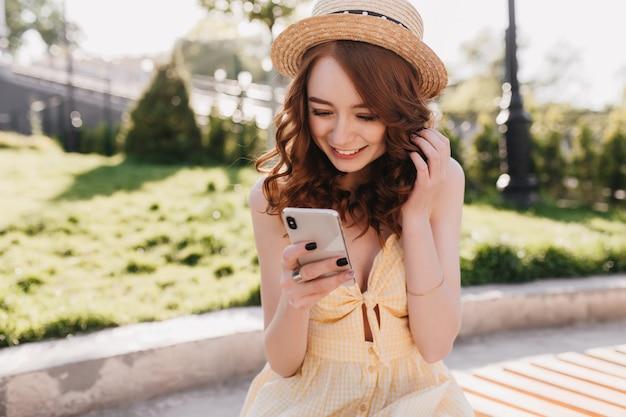 Menina ruiva animada em mensagem de texto de chapéu com sorriso. retrato ao ar livre da senhora ruiva sensual posando com seu smartphone no parque.
