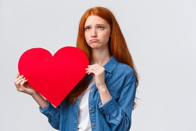 Menina ruiva carismática segurando coração com expressão triste
