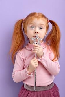 Menina ruiva caucasiana surpresa segurando uma varinha mágica olhando para frente em um roxo pastel