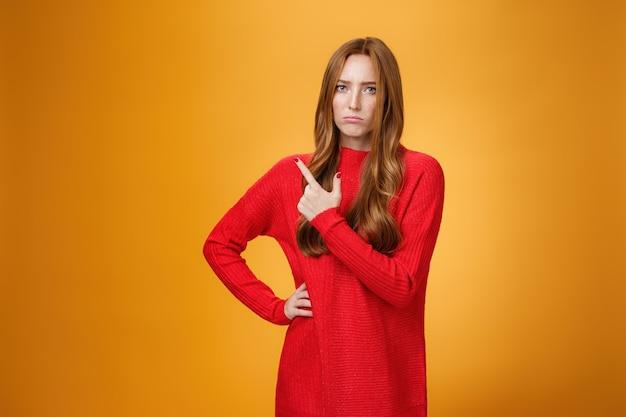 Menina ruiva chateada e desapontada com um suéter vermelho apontando para o canto superior esquerdo ou atrás, carrancuda, parecendo sombria e zangada, ciumenta e mal-humorada contra um fundo laranja