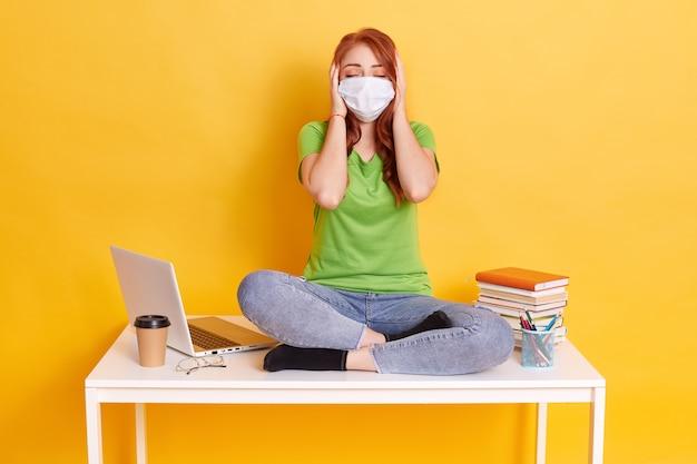 Menina ruiva com máscara médica sentada com as pernas cruzadas na mesa branca, cobrindo as orelhas com as palmas das mãos e mantendo os olhos fechados, vestindo jeans e camiseta, rodeada de lap top, café, canetas