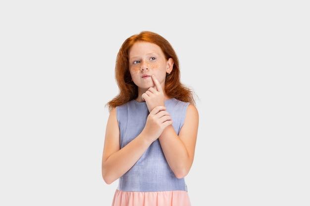 Menina ruiva com roupa casual isolada no fundo branco do estúdio conceito de infância