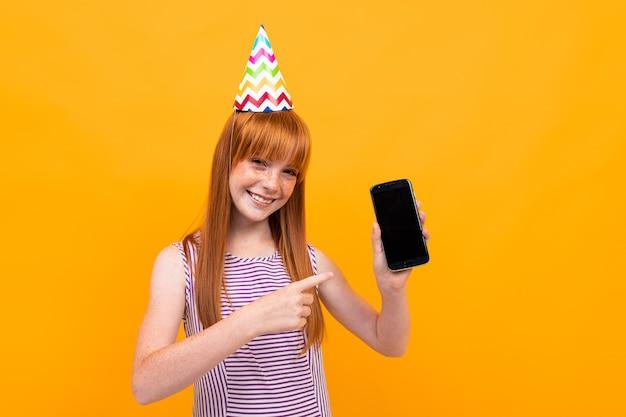 Menina ruiva com um boné festivo na cabeça segurando um telefone