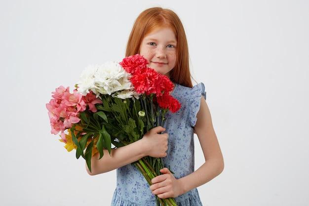 Menina ruiva de petite sardas do retrato, sorrindo e parece fofa, usa um vestido azul, segura o buquê e fica sobre um fundo branco.