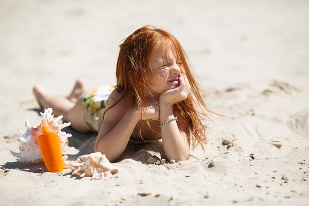 Menina ruiva deitada na areia tomando banho de sol