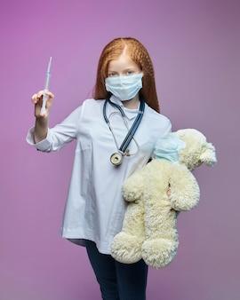 Menina ruiva e um ursinho de pelúcia com máscaras médicas, a criança segurando uma seringa