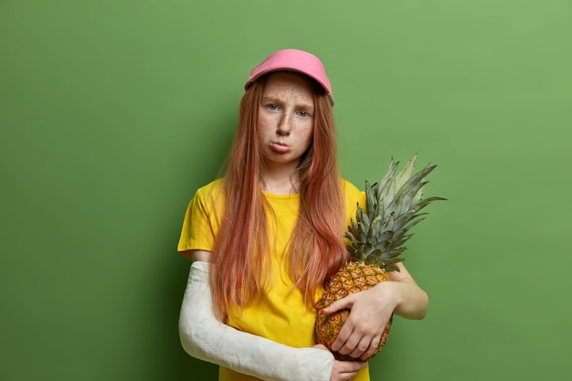 Menina ruiva sardenta ofendida e triste sendo punida pelos pais, segura um suculento abacaxi, franze os lábios e parece sombria, teve trauma durante a prática de esporte arriscado, posa contra parede verde. Foto gratuita