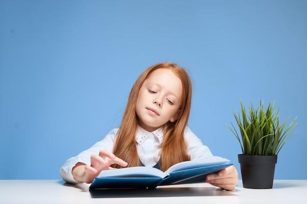 Menina ruiva sentada à mesa com um livro nas mãos, aprendendo lições