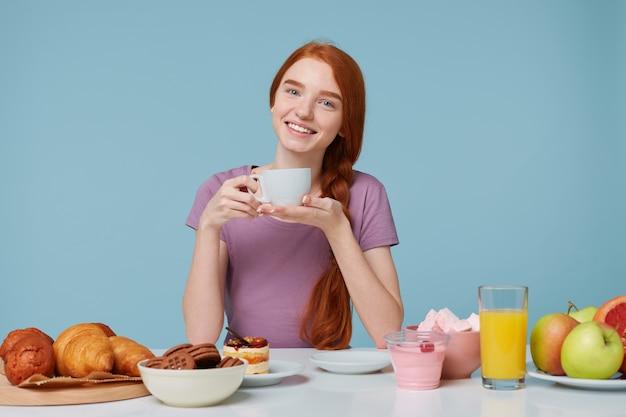 Menina ruiva sentada a uma mesa com a cabeça ligeiramente curvada, sorrindo segurando um copo branco com uma bebida deliciosa nas mãos