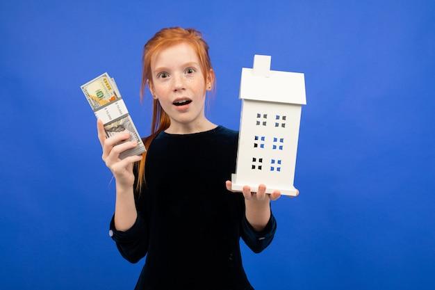 Menina ruiva surpresa com dinheiro e uma casa azul. comprar um imóvel