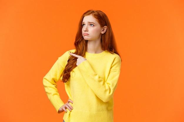Menina ruiva triste com ciúmes ou inveja na camisola amarela, olhando para a coisa desejada