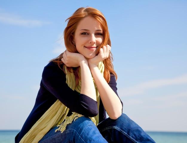 Menina ruivo bonita nova na praia no tempo de mola.