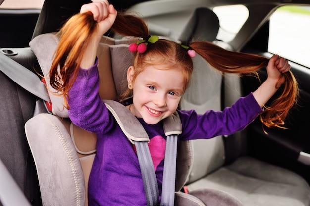 Menina ruivo pequena do bebê que sorri ao sentar-se em um banco de carro da criança.