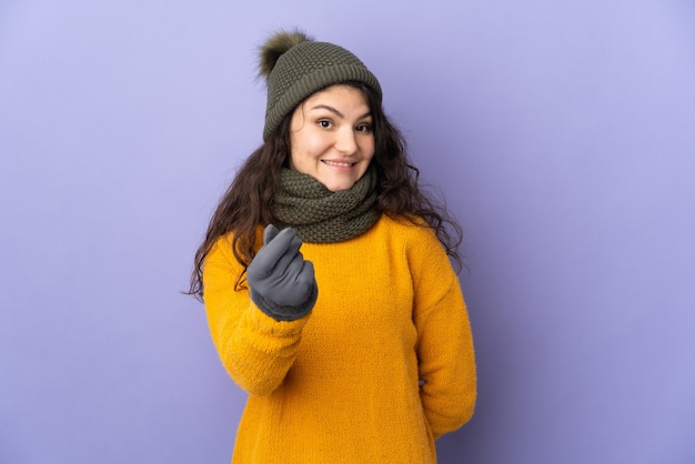Menina russa adolescente com chapéu de inverno isolada em fundo roxo fazendo gesto de dinheiro