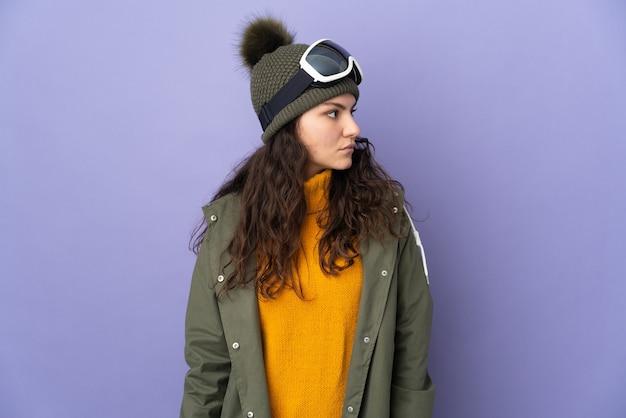 Menina russa adolescente com óculos de snowboard isolada em um fundo roxo olhando para o lado