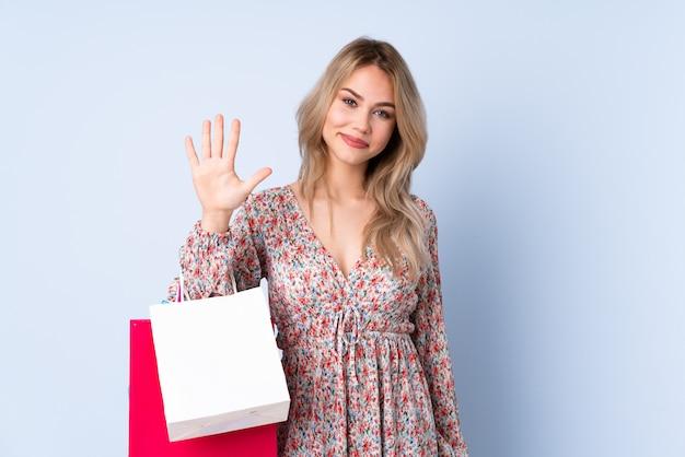 Menina russa adolescente com saco de compras na parede azul, contando cinco com os dedos
