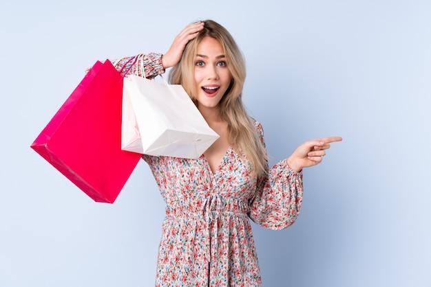 Menina russa adolescente com saco de compras na parede azul surpreso e apontando o dedo para o lado