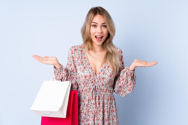 Menina russa adolescente com sacola de compras isolada em azul