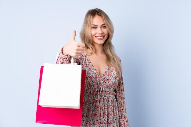 Menina russa adolescente com sacola de compras na parede azul com polegares para cima porque algo bom aconteceu