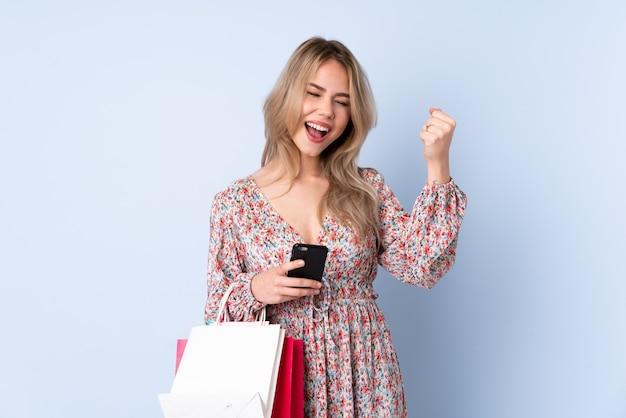 Menina russa adolescente com sacola de compras na parede azul com telefone em posição de vitória