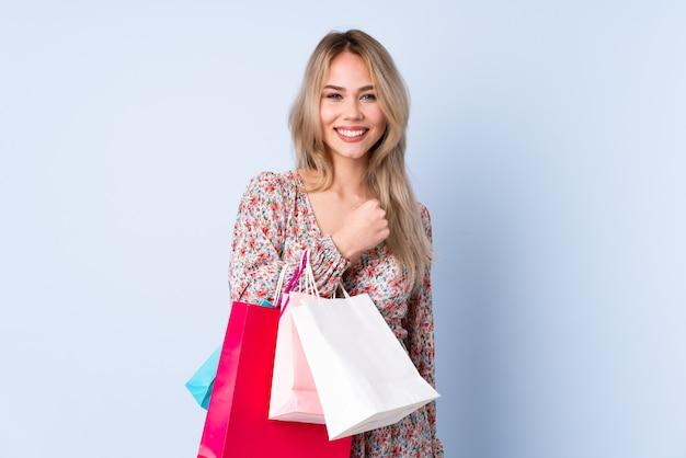 Menina russa adolescente com sacola de compras na parede azul comemorando uma vitória