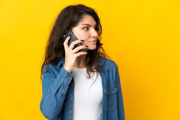 Menina russa adolescente isolada na parede amarela, conversando com alguém ao telefone celular