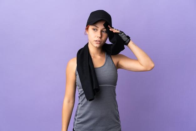 Menina russa adolescente isolada na parede roxa com toalha esportiva
