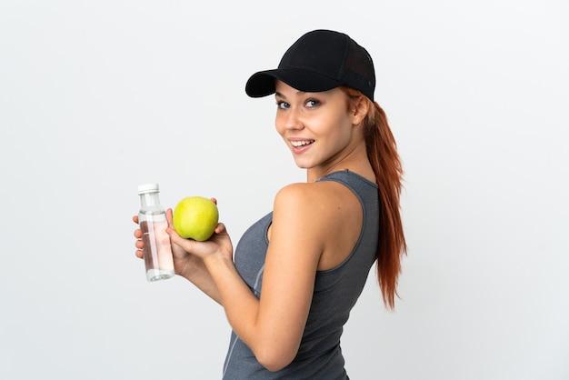 Menina russa adolescente isolada no fundo branco com uma maçã e uma garrafa de água