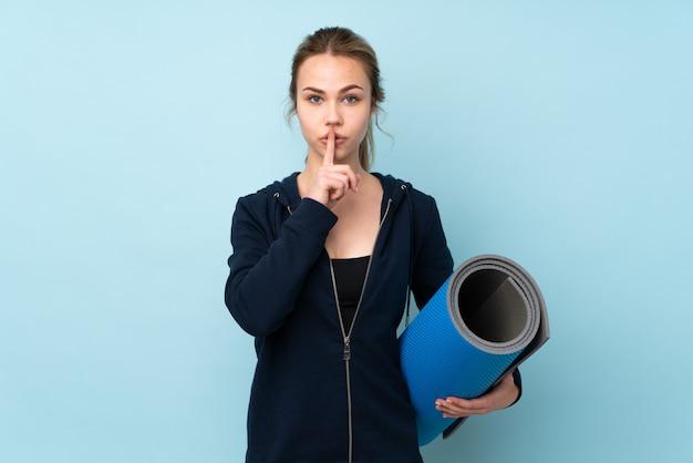 Menina russa adolescente segurando o tapete na parede azul, mostrando um sinal de gesto de silêncio colocando o dedo na boca