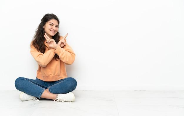 Menina russa adolescente sentada no chão sorrindo e mostrando sinal de vitória